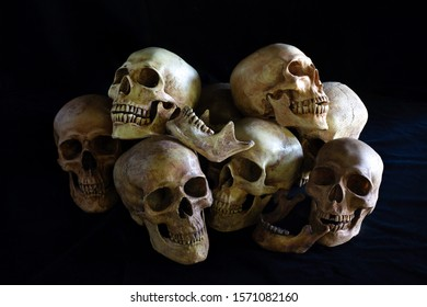 Pile of skull on black background and black cloth floor, Still Life style
