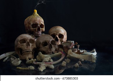 Pile of skulls  and bone and candle on head skull on dark background / Still life style