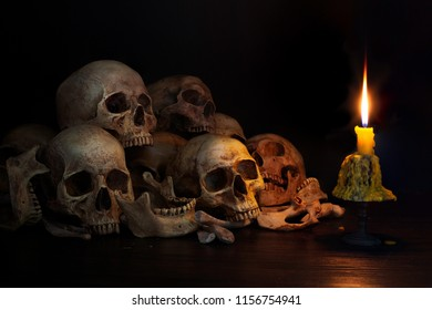 Pile of skulls with bones and Candle which has flame to be bright in the dark light room / Still Life image and select focus