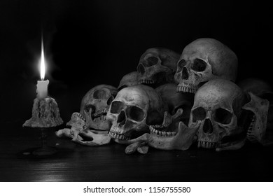 Pile of skulls with bones and Candle which has flame to be bright in the dark light room / Still Life image and select focus,Adjustment color black and white