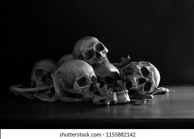 Pile of skulls and bones put on dark wooden plank which has dim light and the dark wall background / Selective focus, Still Life Image and space for texts and Adjustment color black and white