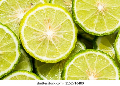 Pile of sliced bergamots randomly arranged, lemon-like texture.
