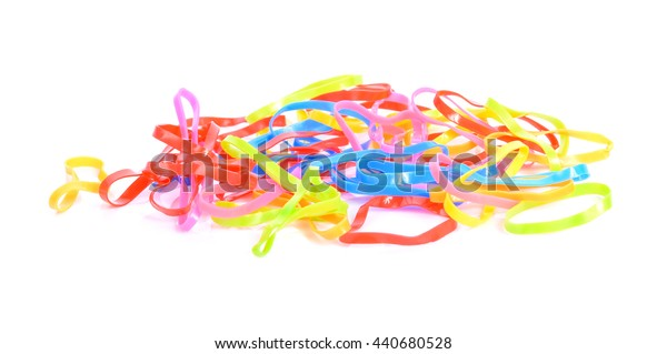 Pile of small round colorful rubber bands for making rainbow loom bracelets isolated on white background