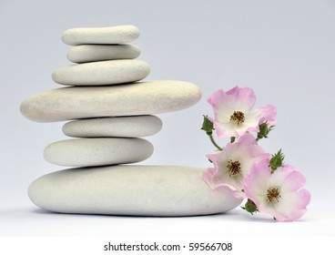 Pile of smooth stones with delicate red flower