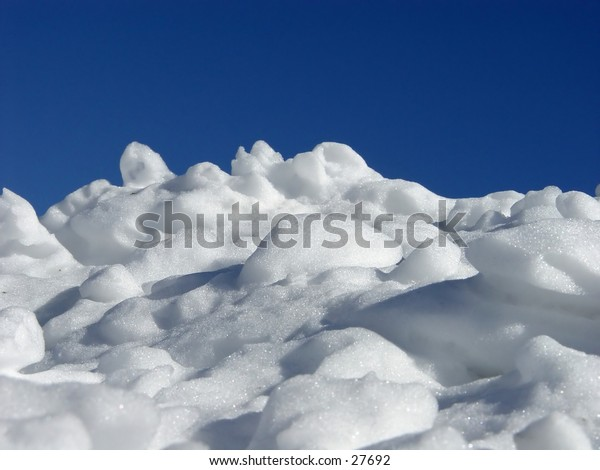Pile of snow with a blue sky as the background