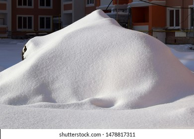 a pile of snow at the construction site, covered with white snow after a blizzard and snowfall, closeup