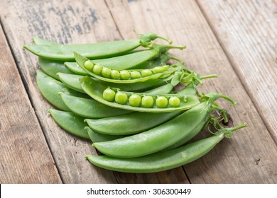 Pile of snow peas on wood background.
