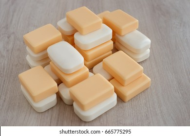 A pile of soap on a wooden background. A solid soap of white and yellow color is stacked on a wooden background. Soap for hygiene and cleanliness. The soap is made in the form of a pyramid.