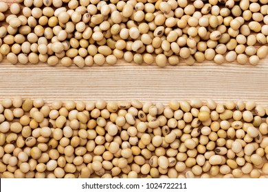 A pile of soybeans, divided into two rows on the wood table. Soybean is a leguminous plant native to Asia, widely cultivated for its edible seeds. with copy space for your text.