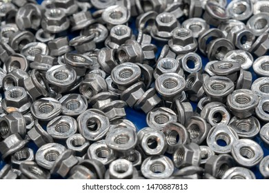 The pile of the special nuts in the container box. The nuts and bolts manufacturing process.
