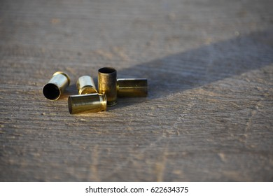 Pile of spend brass bullet casings on weathered wood in sunlight