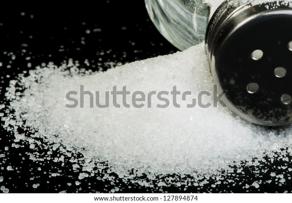 Pile of spilled salt and saltshaker black isolated