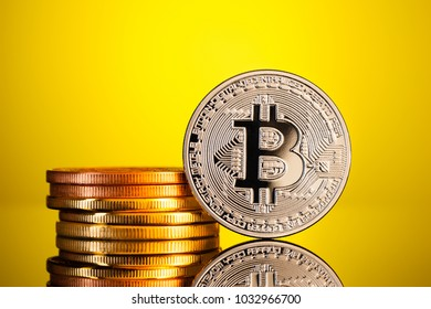 a pile or stack of bitcoin physical silver end golden coins over a yellow background. Bitcoin is a digital cryptocurrency
