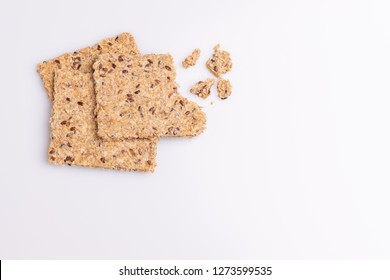 Pile stack of diet flax seed whole grain crackers isolated on white background, soft light, top view, copy space