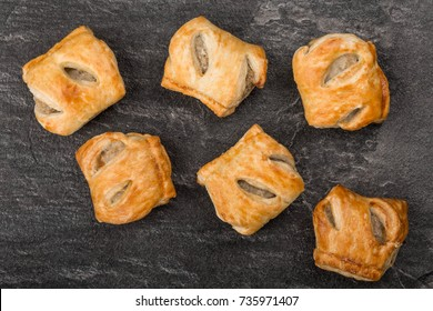 Pile Stack or Selection of Pork Sausage Rolls Savoury Snacks In Pastry On A Black Kitchen Tile