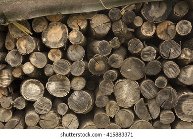 Pile of stacked, dark, brown and grey logs background. Close-up of stack of wood.
