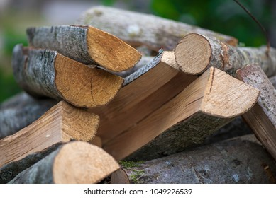 A pile of stacked firewood, prepared for heating the house. Gathering fire wood for winter or bonfire.