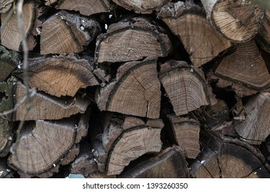 A pile of stacked firewood, prepared for heating the house. Firewood harvested for heating in winter. Chopped firewood on a stack. Firewood stacked and prepared for winter Pile of wood logs.