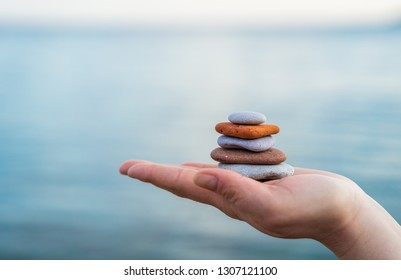 Pile of stacked held by a female hand on a seaside
