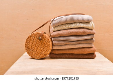 Pile of ,stacked knitted clothes sweaters, , bamboo round handbag on a wooden background. Autumn and winter clothes.