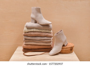 Pile of ,stacked knitted clothes sweaters, high hell shoes, bamboo round handbag on a wooden background. Autumn and winter clothes.