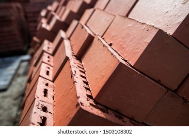 Pile of stacked new red bricks. Clay brick blocks ready for construction.