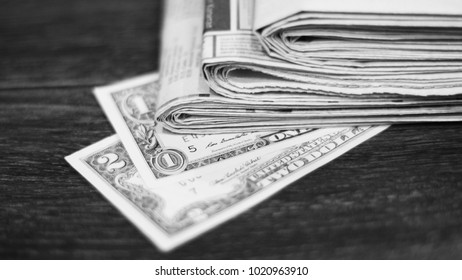 Pile of stacked newspapers and 2 bills of one and two dollars. Fresh daily papers with business news and national USA money on wooden table. American bank note and journals, selective focus, side view