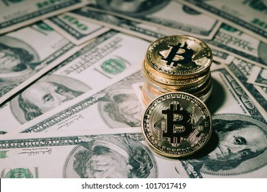 Pile of stacking Golden bitcoin on one hundred dollar banknotes. single coin facing the camera in sharp focus with shading on the icon letter B on the face of the bitcoin, electronic money concept