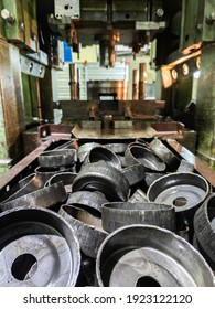 pile of stamped thick sheet black metal round parts after a hood operation in front of forming press with die tooling