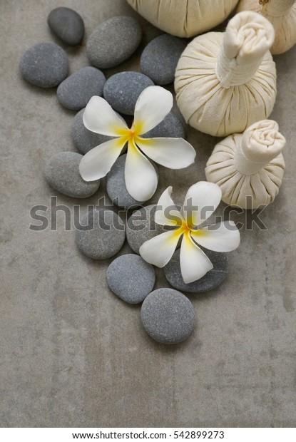 Pile of stone with frangipani,massage ball on grey background.