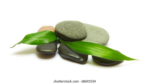 Pile of stones and bamboo leafs isolated on white