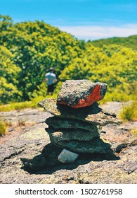 A pile of stones become a cairn as a marker on The great mountain iron trail with beautiful summer views background in  New England Canaan New Hampshire United States.