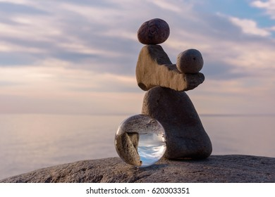 Pile of stones and crystal ball on the seashore