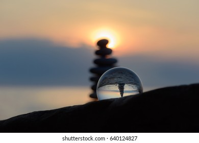 Pile of stones and crystal ball on the seashore in evening