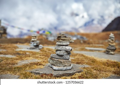 Pile of stones and Tibetan prayer flags Lung Ta at the Mardi Himal Base Camp at cloudy peaks of Himalaya Mountains in Nepal