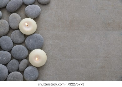 pile of stones with two white candle on grey background