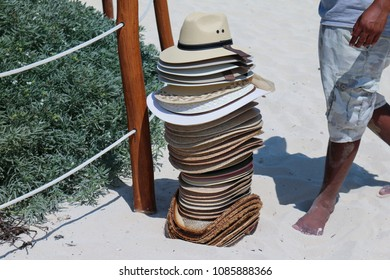 A pile of straw hats on a beach sand.