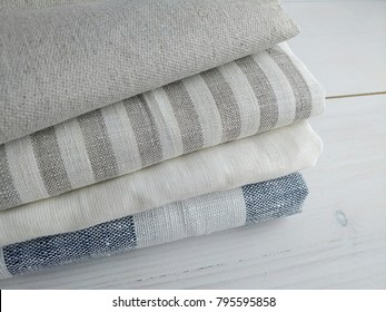 Pile of striped white grey blue linen cotton fabrics, handmade kitchen, hand towels on white wooden background. Different colours. Food photo props. Natural linen cotton fabric.
