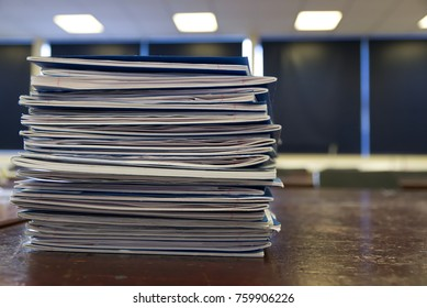Pile of student notebooks in a school classroom on an old wooden desk