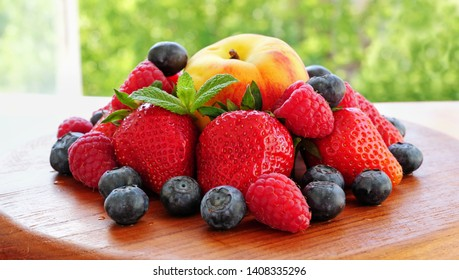 Pile of summer berries and fruits over wooden board. Ripe strawberries, raspberries, blueberries and peach on a table