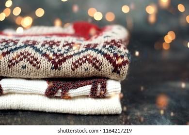Pile of sweaters. Winter Christmas knitting bokeh blur backg