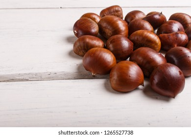 pile of sweet chestnuts on white wooden background with copy space, top view.