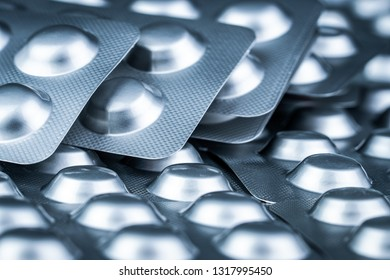Pile of tablets pill in blister packaging to protect medicine from light. Silver aluminium foil blister pack. Pharmaceutical industry. Pharmacy products. Drug recall and withdrawal from market concept