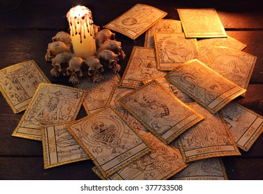 Pile of the tarot cards in candle light. Halloween and magic still life, fortune telling seance or black magic ritual with mysterious occult and esoteric symbols, divination rite