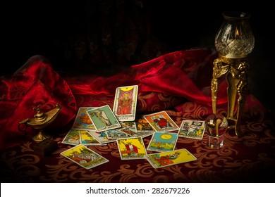 Une pile de cartes de tarot est éparpillée et étalée sur une table entourée de multiples objets occultes.