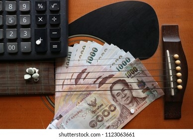 Pile of Thai Baht money with mixed pills medicine and calculator on wood acoustic guitar