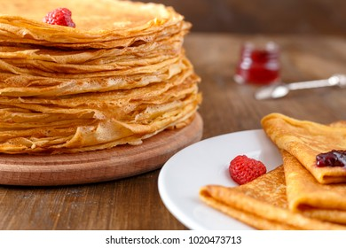 A pile of thin hot pancakes with fruits of strawberries on a wooden table, a few pancakes on the plate with jar of jam