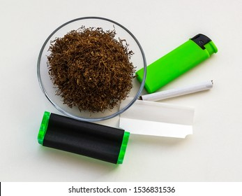 Pile of tobacco in glass saucer, green cigarette rolling machine, paper, one cigarette and green lighter on a white table. Making cigarettes with pipe tobacco. Flat lay.