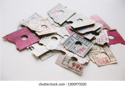pile of torn red, grew, yellow movie ticket stubs from a 99-cent cinema in Connecticut in 1980s against white background