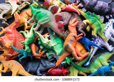 Pile of toy plastic dinosaurs.
